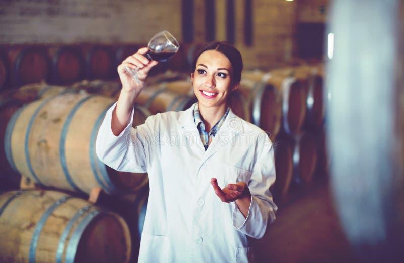Vrouw die het glas van de laagholding wijn op wijnmakerij dragen stock afbeelding