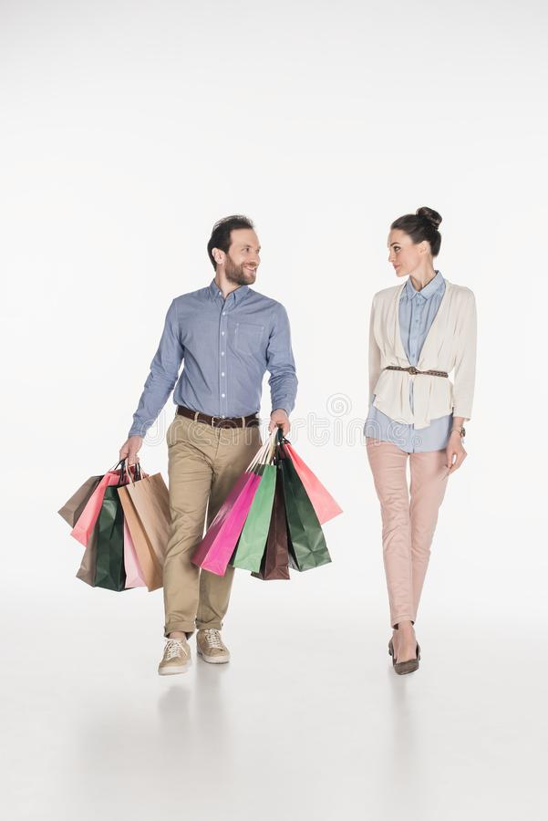 vrouw die het glimlachen van echtgenoot dragende het winkelen zakken bekijken royalty-vrije stock fotografie