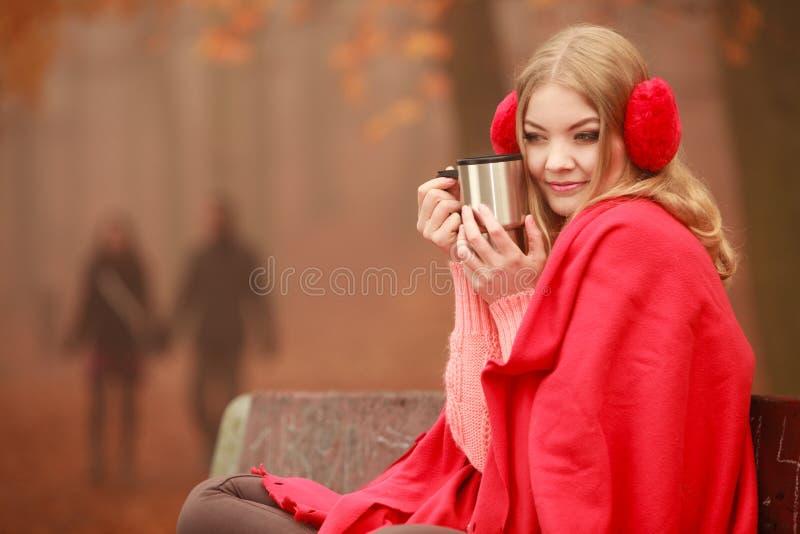 Vrouw die het hete koffie ontspannen in de herfstpark drinken royalty-vrije stock afbeelding