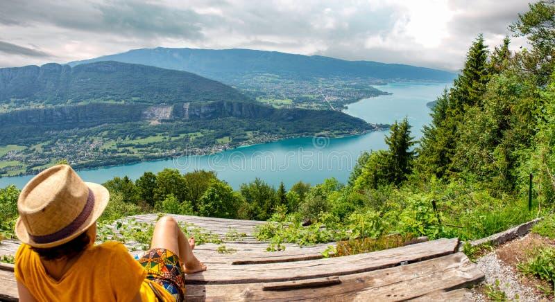 Vrouw die het landschap van Meer Annecy bekijken stock afbeelding