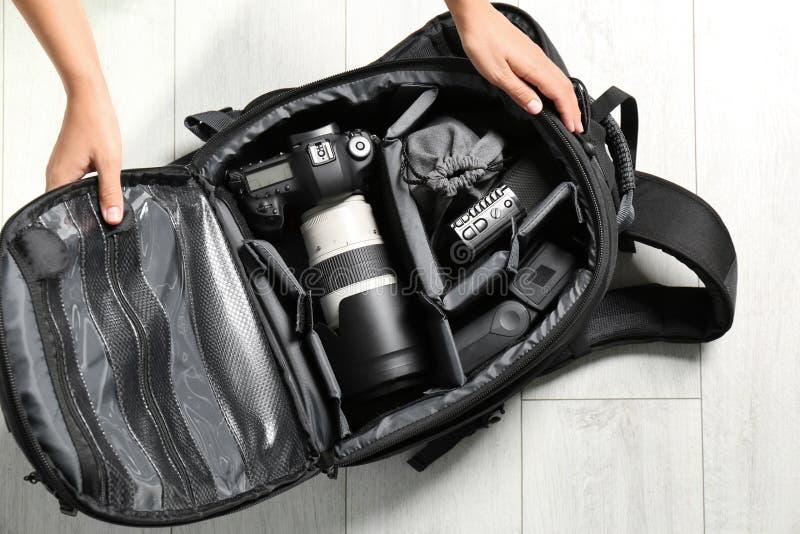 Vrouw die het materiaal van de professionele fotograaf zetten in rugzak op vloer stock foto