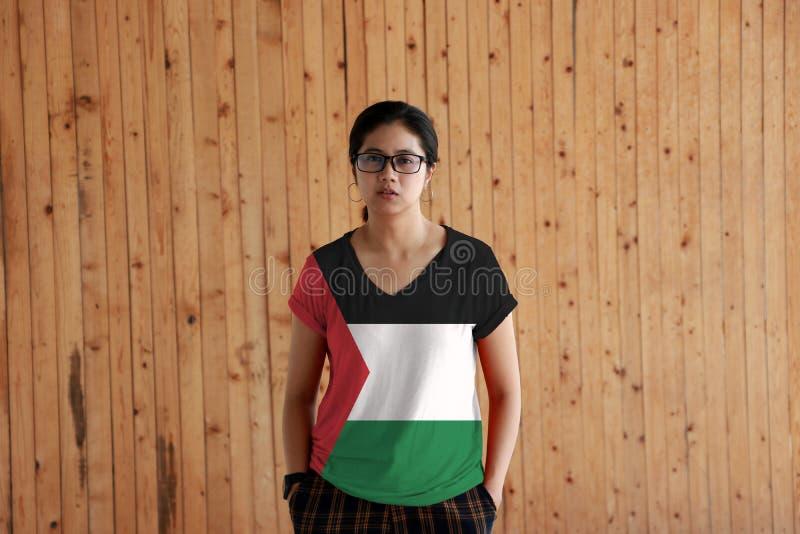 Vrouw die het overhemd van de de vlagkleur van Palestina draagt en zich met twee de bevindt dient broekzakken op de houten muurac stock afbeeldingen
