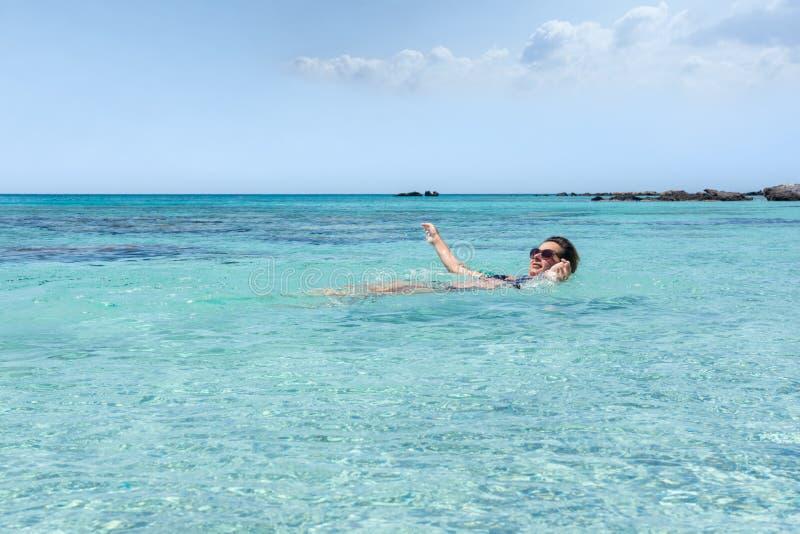 Vrouw die in het overzees bij Elafonisi-strand, in het eiland van Cr zwemmen stock fotografie