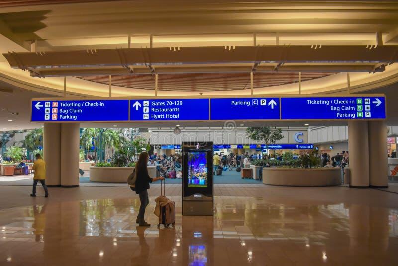 Vrouw die het scherm van het Bezoekercentrum en hoogste mening van Etikettering en Controle blauw teken in Orlando International  stock foto