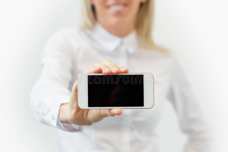 Vrouw die het scherm van de lege mobiele telefoon horizontaal tonen stock fotografie