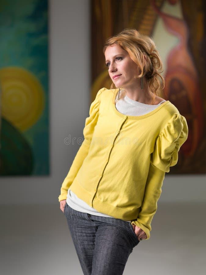 Vrouw die het schilderen in een kunstmuseum analyseren royalty-vrije stock afbeelding