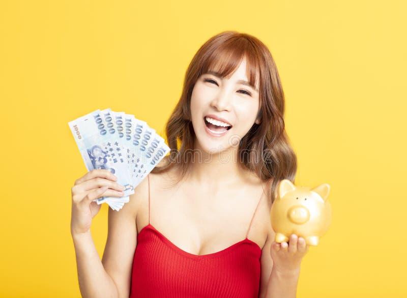 Vrouw die het spaarvarken tonen terwijl het houden van geld royalty-vrije stock afbeelding