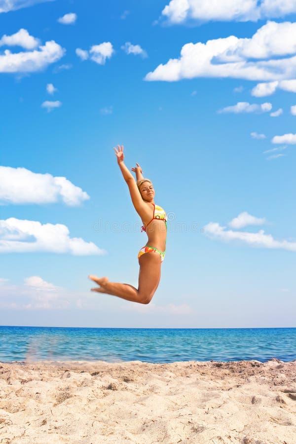 Vrouw die in het strand springt royalty-vrije stock afbeelding