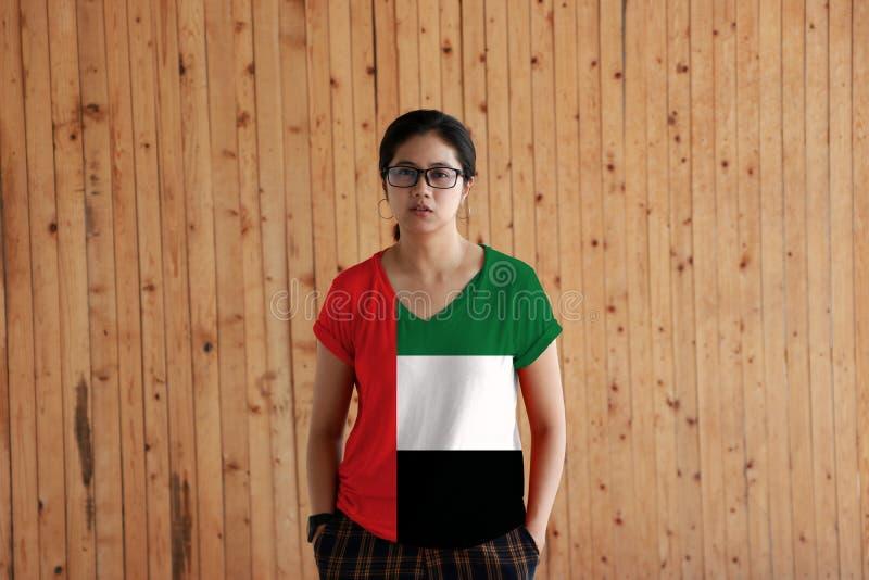 Vrouw die het Verenigde Arabische overhemd van de de vlagkleur van Emiraten dragen en zich met twee de bevinden dient broekzakken royalty-vrije stock fotografie