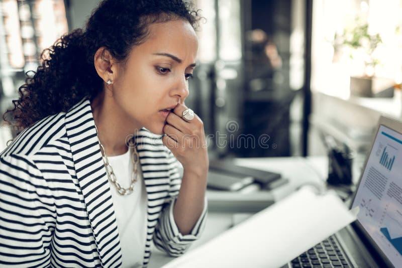 Vrouw die in het vermoeid werken en nadenkende bureaugevoel stock foto's
