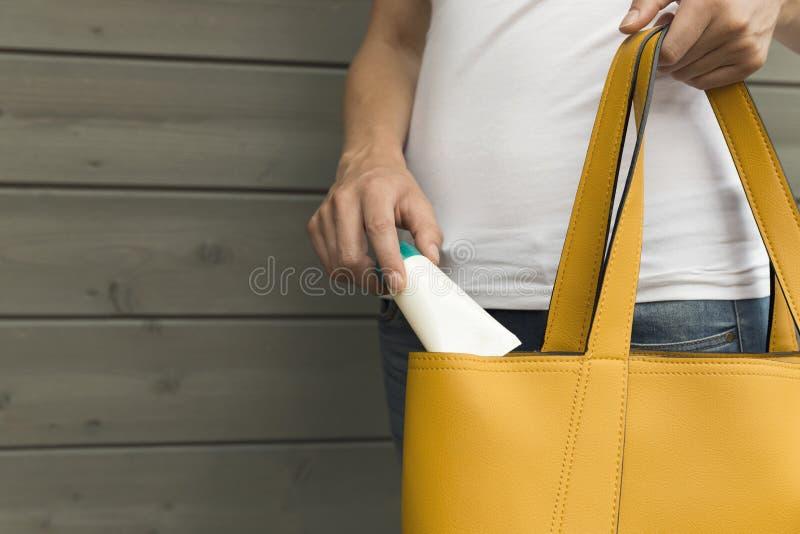 Vrouw die het zonscherm, handroom nemen uit gele beurs Zon pro royalty-vrije stock afbeelding