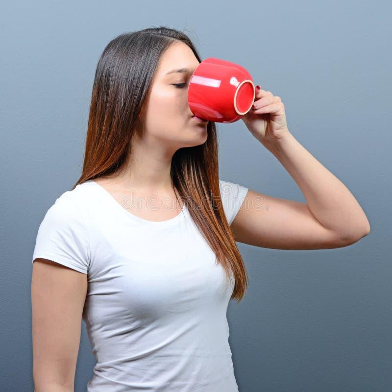 Vrouw die hete drank drinken tegen grijze achtergrond royalty-vrije stock foto