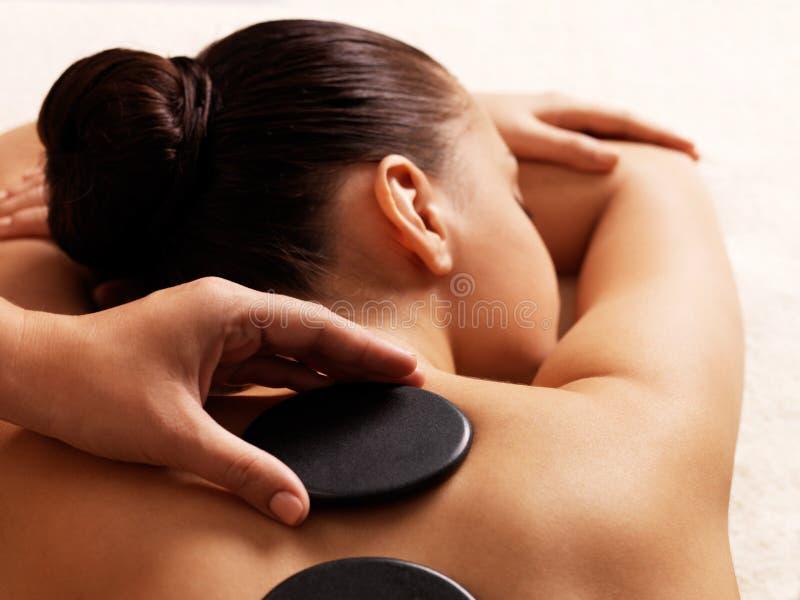 Vrouw die hete steenmassage in kuuroordsalon krijgt. stock afbeeldingen