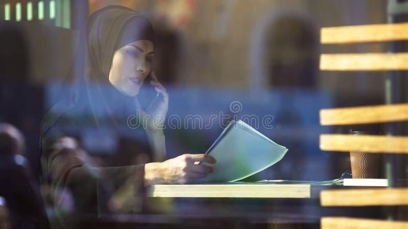 Vrouw die hijab door contract in koffie kijken die partner, vrije Moslimdame roepen stock foto