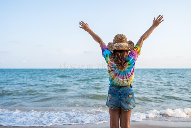 Vrouw die hoed met opgeheven wapens dragen status op overzees strand stock afbeeldingen