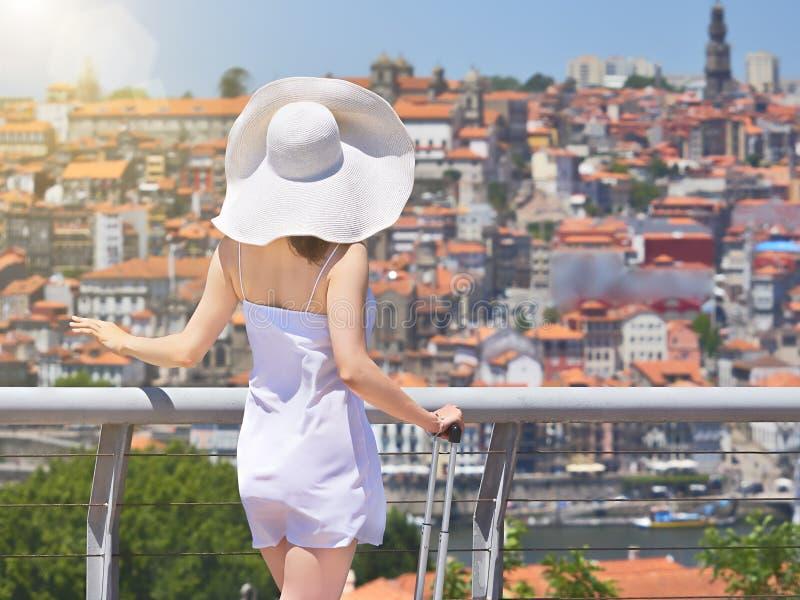 Vrouw die in hoed met reiszak van cityscape van Porto Stad genieten Achter mening royalty-vrije stock foto's