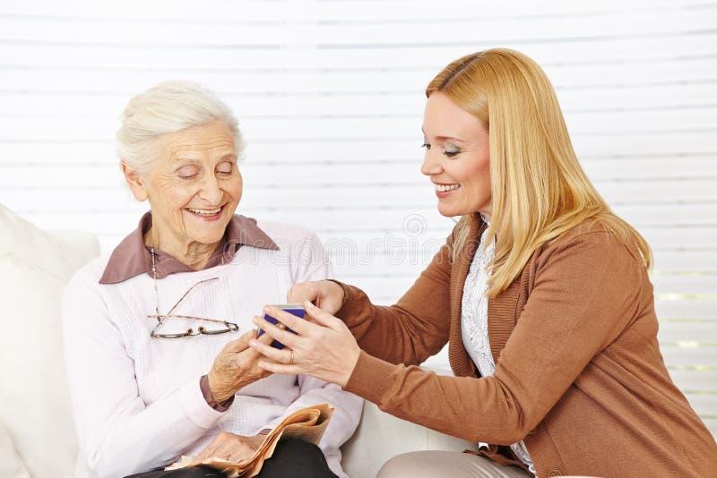 Vrouw die hogere vrouw met haar helpen royalty-vrije stock foto