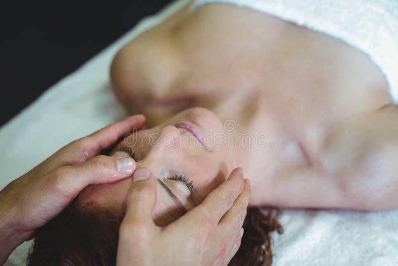 Vrouw die hoofdmassage van fysiotherapeut ontvangen stock foto