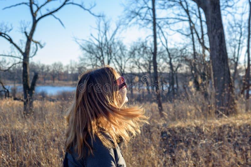 Vrouw die in hout met blondehaar lopen die in zonneschijn blazen stock afbeelding