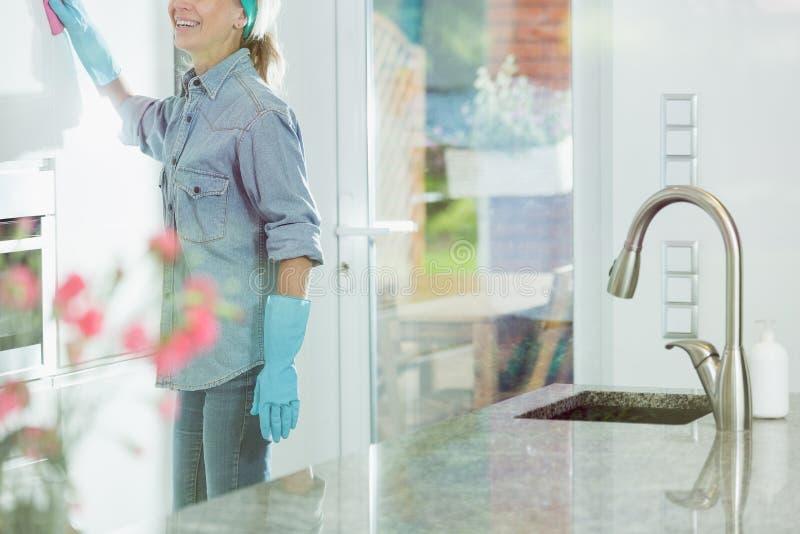 Vrouw die huis het schoonmaken plichten doen stock afbeelding