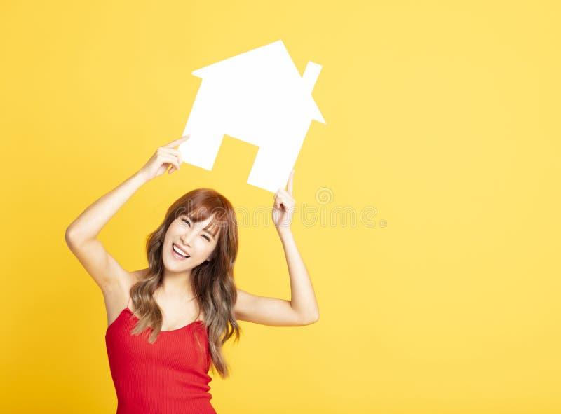 vrouw die huisteken voor nieuwe huisconcepten toont royalty-vrije stock afbeeldingen