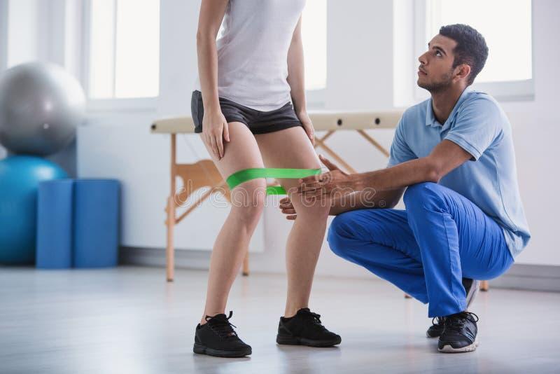 Vrouw die hurkzit met een oefeningsband doen die door haar persoonlijke trainer wordt gesteund stock fotografie