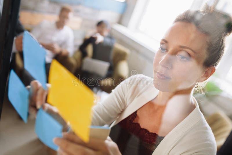 Vrouw die ideeën voorstellen aan collega's tijdens vergadering stock afbeelding