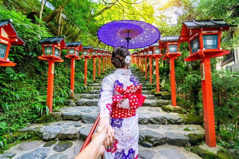 Vrouw die Japanse traditionele de man ` s van de kimonoholding hand dragen en hem leiden tot Kifune-heiligdom, Kyoto in Japan stock foto's