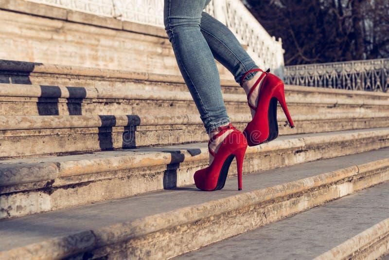 Vrouw die jeans en rode hoge hielschoenen in oude stad draagt De vrouwen dragen hoge hielen lopen omhoog treden Sexy benen in rod royalty-vrije stock fotografie