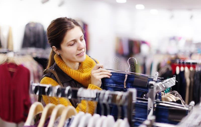 Vrouw die jeans kiezen bij winkel royalty-vrije stock afbeeldingen