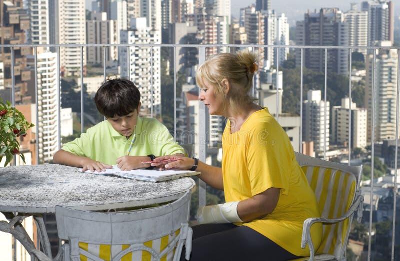 Vrouw die jongen helpen schrijven - Horizontaal stock afbeeldingen