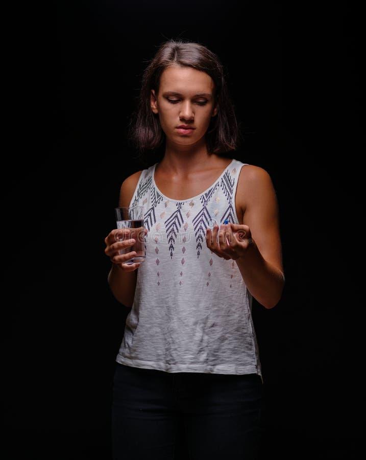 Vrouw die kalmeringsmiddelen nemen Een patiënt met pillen op een zwarte achtergrond Spanning, bezorgdheid, het concept van de dep stock foto