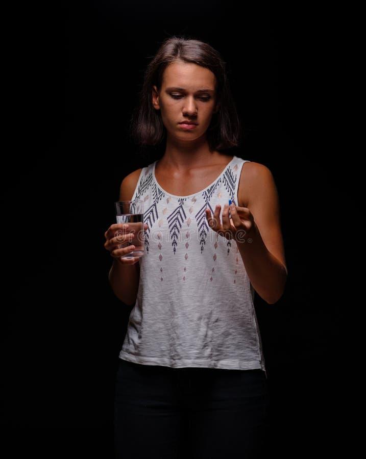 Vrouw die kalmeringsmiddelen nemen Een patiënt met pillen op een zwarte achtergrond Spanning, bezorgdheid, het concept van de dep royalty-vrije stock afbeelding