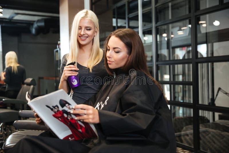 Vrouw die kapsel bespreken met haar kapper in de herenkapper royalty-vrije stock afbeeldingen