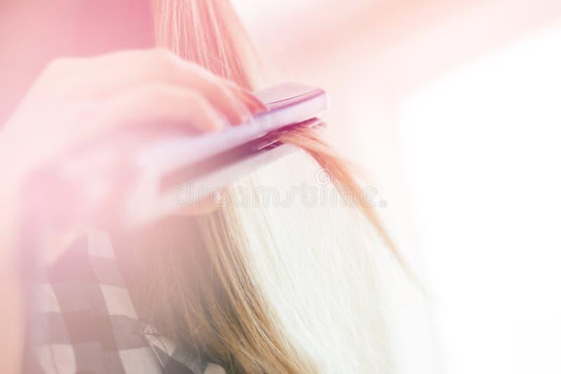 Vrouw die kapsel met haargelijkrichter doen, het lichte stemmen stock foto's