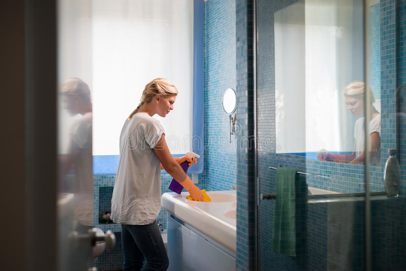 Vrouw die karweien thuis doet en badkamers schoonmaakt royalty-vrije stock afbeelding