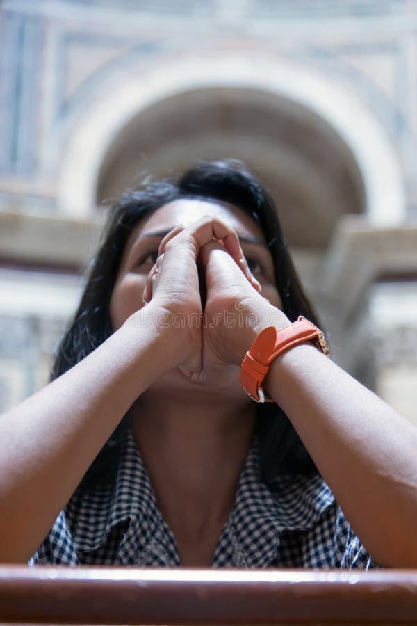 Vrouw die in kerk bidt stock foto's