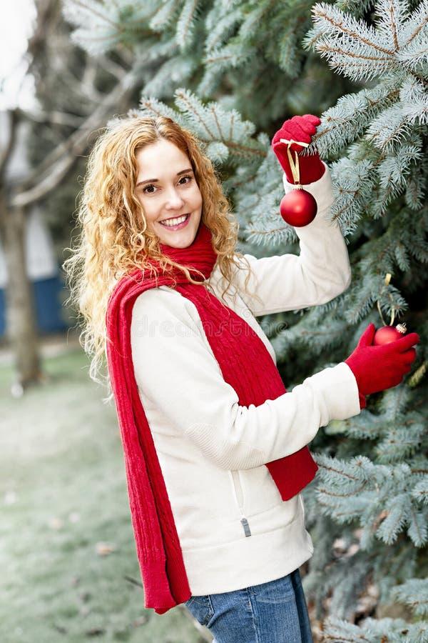 Vrouw die Kerstboom buiten verfraaien royalty-vrije stock afbeeldingen