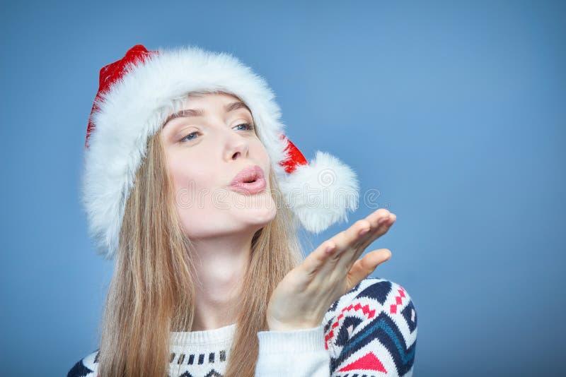 Vrouw die Kerstmanhoed dragen die bij open handpalm blazen met exemplaarruimte royalty-vrije stock foto