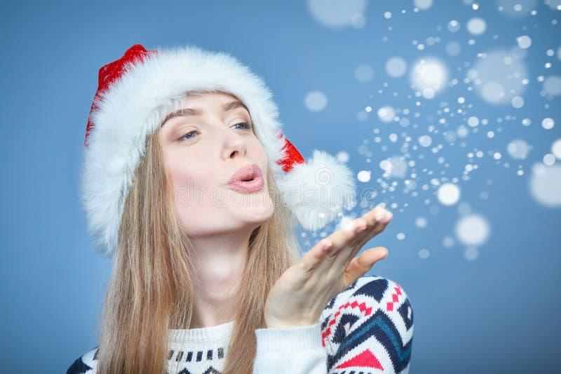 Vrouw die Kerstmanhoed dragen die bij open handpalm blazen met sneeuw royalty-vrije stock afbeelding