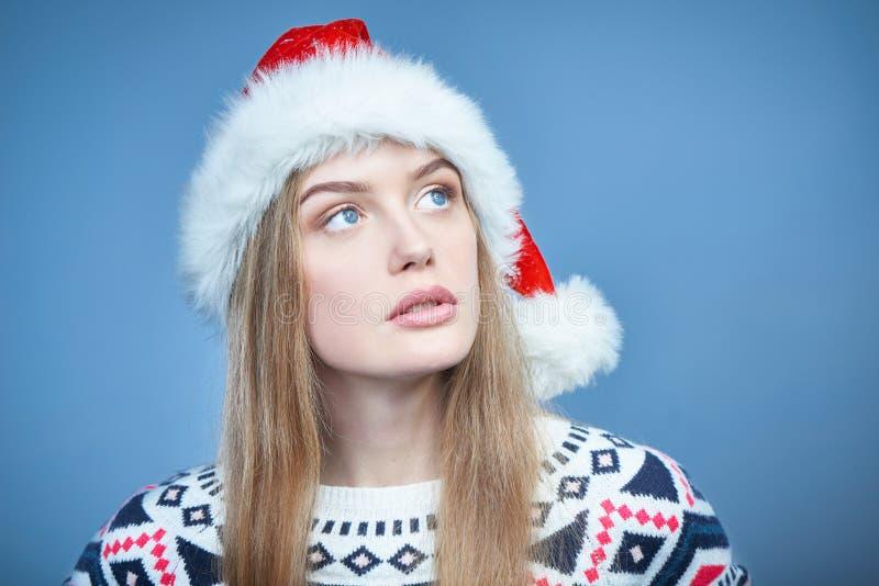Vrouw die Kerstmanhoed dragen die weg exemplaarruimte bekijken met rente stock foto