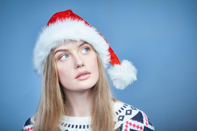 Vrouw die Kerstmanhoed dragen die weg exemplaarruimte bekijken met rente stock fotografie
