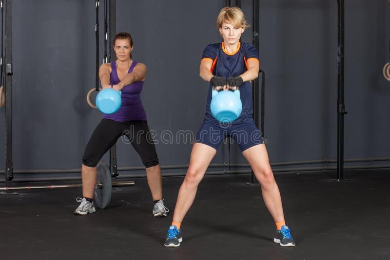 Vrouw die kettlebell - geschiktheid opleiding slingeren stock foto