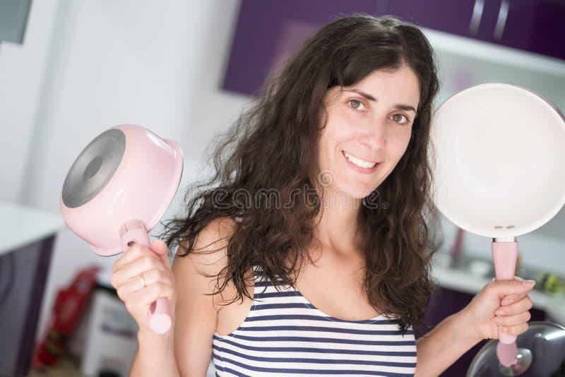 Vrouw die in keuken met pan bij camera glimlachen royalty-vrije stock foto's