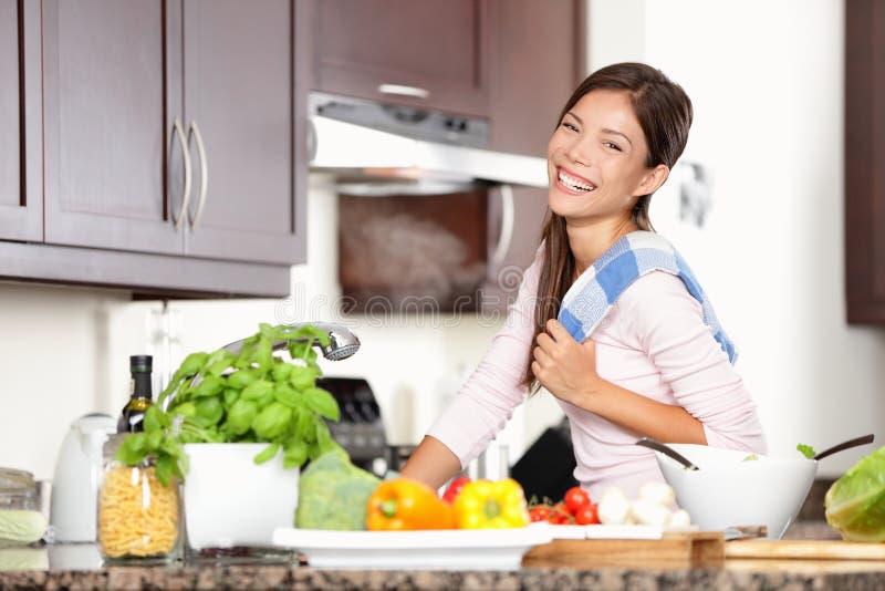 Vrouw die in keuken voedsel gelukkig maakt royalty-vrije stock fotografie