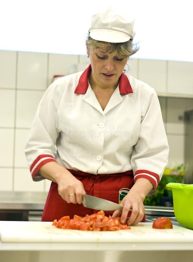 Vrouw die in keuken werkt stock afbeelding