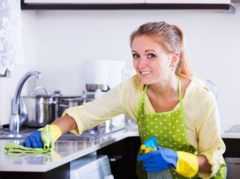 Vrouw die keukenbovenkant thuis bestrooien royalty-vrije stock afbeeldingen