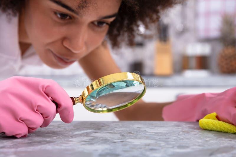 Vrouw die Keukenteller bekijken met Vergrootglas royalty-vrije stock afbeelding
