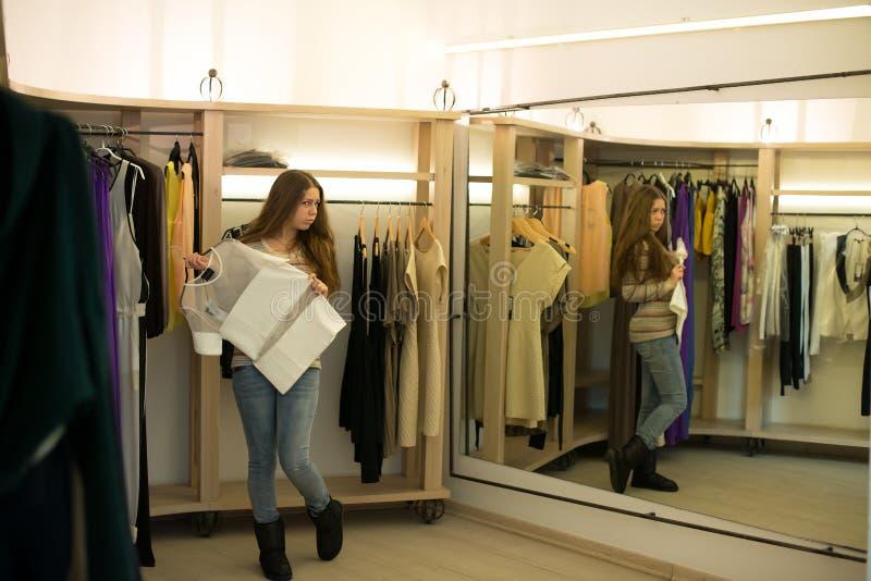 Vrouw die kiezend kleding die in onzekere spiegel kijken winkelen stock fotografie