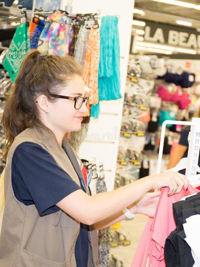 Vrouw die kleding kiezen tijdens het winkelen bij de kledingswinkel van de kledingstukkenkleding stock foto's